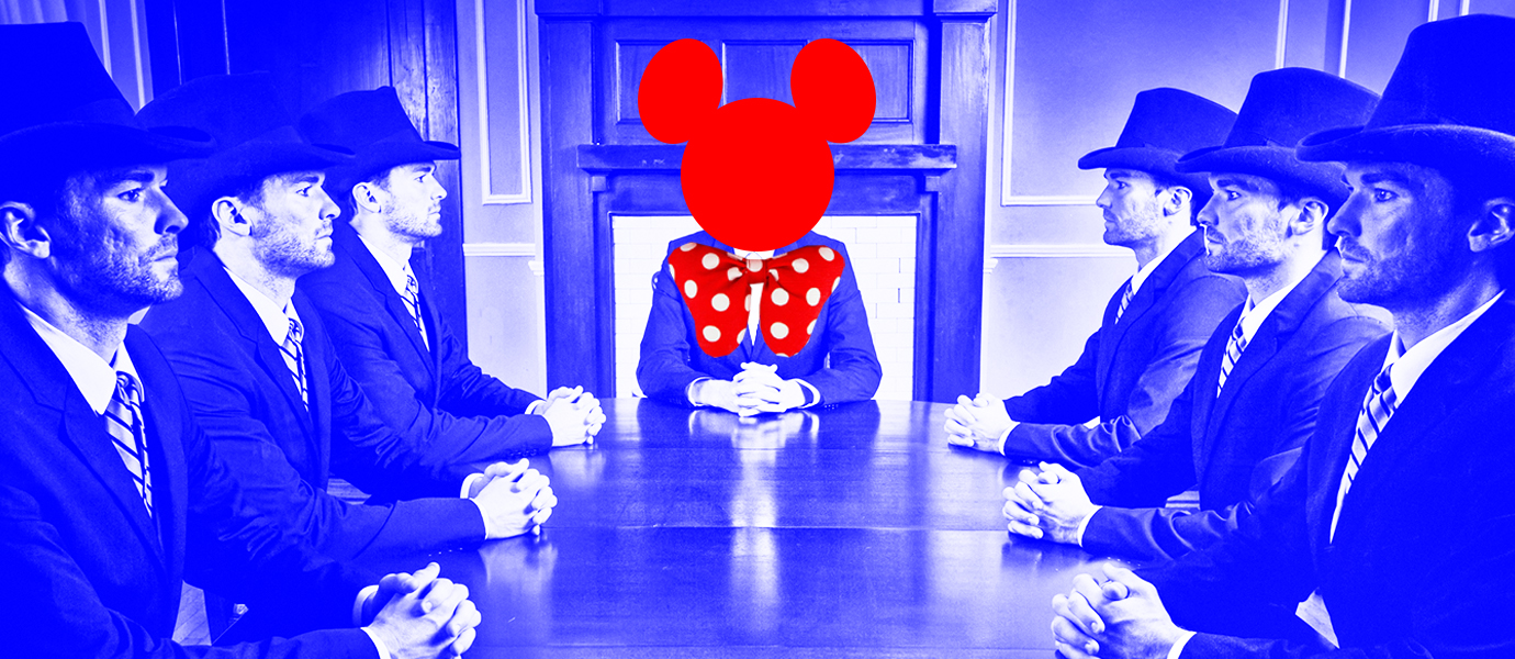 Blue photo of men sitting at a table with Mickey Mouse